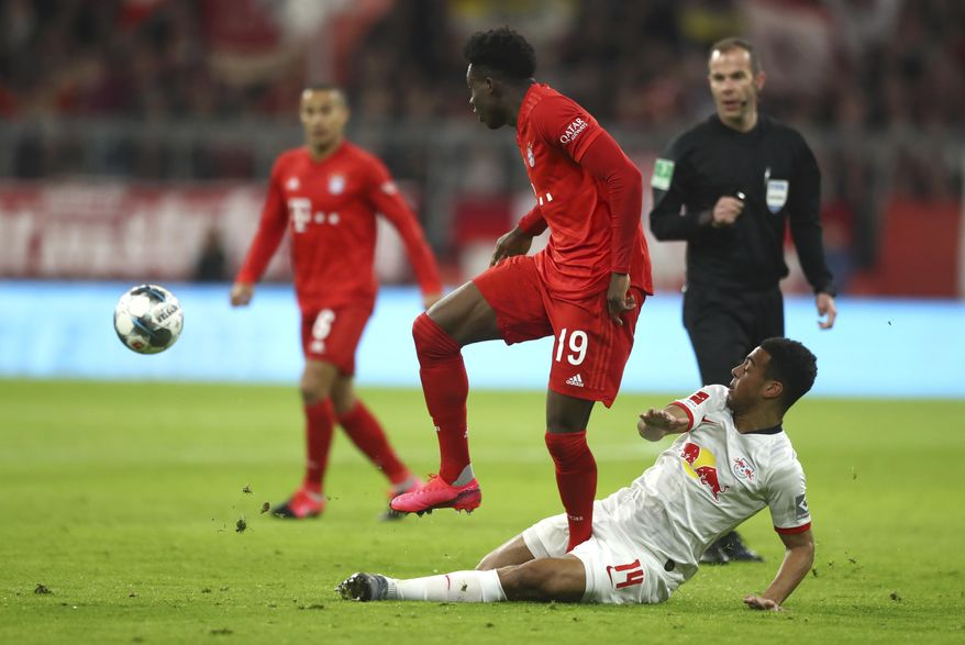 Bayern's Alphonso Davies, centre, and Leipzig's Tyler Adams challenge for the ball during the German Bundesliga soccer match between Bayern Munich and RB Leipzig at the Allianz Arena in Munich, Germany, Sunday, Feb. 9, 2020. (AP Photo/Matthias Schrader)