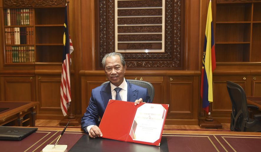 In this photo released by Malaysia's Department of Information, the country's new Prime Minister Muhyiddin Yassin poses for pictures on his first day at the prime minister's office in Putrajaya, Malaysia, Monday, March 2, 2020. (Hafiz Itam/Malaysia's Department of Information via AP)