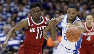 North Carolina State guard Markell Johnson (11) and Duke guard Cassius Stanley (2) chase the ball during the first half of an NCAA college basketball game in Durham, N.C., Monday, March 2, 2020. (AP Photo/Gerry Broome)