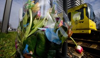 -FILE- In this Tuesday March 19, 2019, file image, a tram passes flowers placed at the site of a shooting incident on a tram, in Utrecht, Netherlands. The trial of a Dutch man of Turkish descent is starting Monday March 2, 2020, for allegedly opening fire on a tram in the central city of Utrecht last year, killing four people in what prosecutors say was a terror attack. (AP Photo/Peter Dejong, File)