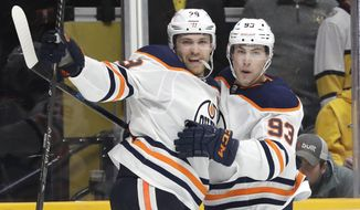 Edmonton Oilers center Leon Draisaitl (29), of Germany, celebrates with Ryan Nugent-Hopkins (93) after Draisaitl scored his second goal of the game against the Nashville Predators in the third period of an NHL hockey game Monday, March 2, 2020, in Nashville, Tenn. (AP Photo/Mark Humphrey)