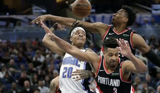 Orlando Magic guard Markelle Fultz (20) passes the ball behind his head as he gets trapped between Portland Trail Blazers center Hassan Whiteside, back right, and guard CJ McCollum (3) during the second half of an NBA basketball game, Monday, March 2, 2020, in Orlando, Fla. (AP Photo/John Raoux)