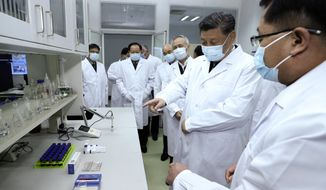 In this photo released by Xinhua News Agency, Chinese President Xi Jinping, second right, wearing a protective face mask, talks to a medical staff members during his visit to the Academy of Military Medical Sciences in Beijing, Monday, March 2, 2020. The number of new virus infections rose worldwide along with fears of a weakening global economy, even as cases in China dropped to their lowest level in six weeks on Monday and hundreds of patients at the outbreak's epicenter were released from hospitals. (Ju Peng/Xinhua via AP)