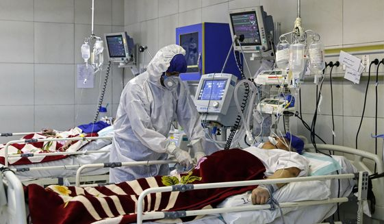 In this Sunday, March 1, 2020 photo, a medic treats a patient infected with coronavirus, at a hospital in Tehran, Iran. A member of a council that advises Iran's supreme leader died Monday after falling sick from the new coronavirus, becoming the first top official to succumb to the illness striking both citizens and leaders of the Islamic Republic. (Ali Shirband/Mizan News Agency via AP)