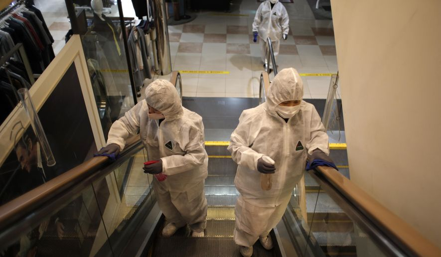 Workers wearing protective gear spray disinfectant as a precaution against the new coronavirus at a department store in Seoul, South Korea, Monday, March 2, 2020. South Korea has the world's second-highest cases. (AP Photo/Lee Jin-man)