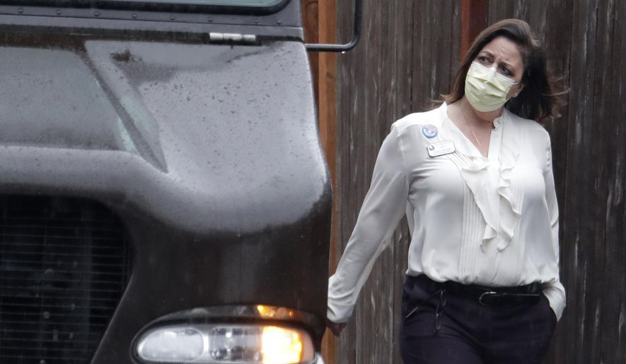 A worker at the Life Care Center in Kirkland, Wash., near Seattle, wears a mask as she walks near a UPS truck during a package delivery, Monday, March 2, 2020. Several of the people who have died in Washington state from the COVID-19 coronavirus were tied to the long-term care facility, where dozens of residents were sick. (AP Photo/Ted S. Warren)