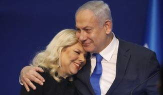 Israeli Prime Minister Benjamin Netanyahu hugs his wife Sara after first exit poll results for the Israeli elections at his party's headquarters in Tel Aviv, Israel, Monday, March. 2, 2020. (AP Photo/Ariel Schalit)
