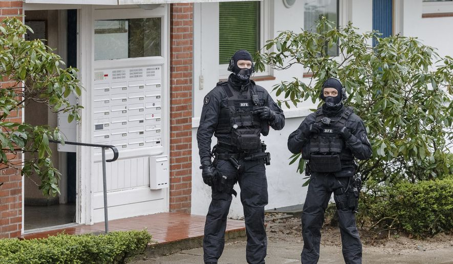 Police officers stay in front of an apartment building in Bad Segeberg, northern Germany, Tuesday, March 3, 2020. German police have raided the homes of 12 people in the German state of Schleswig-Holstein and elsewhere in Germany who are suspected of forming a far-right group that wanted to attack immigrants and foreigners. (Markus Scholz/dpa via AP)