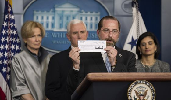 Department of Health and Human Services Secretary Alex Azar, holds a check from President Donald Trump donated to the Department of Health and Human Services during a briefing on coronavirus in the Brady press briefing room of the White House, Tuesday, March 3, 2020, in Washington. With Azar are, from left, White House coronavirus response coordinator Dr. Deborah Birx, Vice President Mike Pence, Azar, and administrator of the Centers for Medicare and Medicaid Services Seema Verma. (AP Photo/Manuel Balce Ceneta)