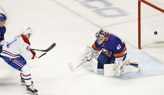 Montreal Canadiens left wing Paul Byron (41) watches his power-play goal go into the net behind New York Islanders goaltender Semyon Varlamov (40) during the second period of an NHL hockey game, Tuesday, March 3, 2020, in New York. (AP Photo/Kathy Willens)