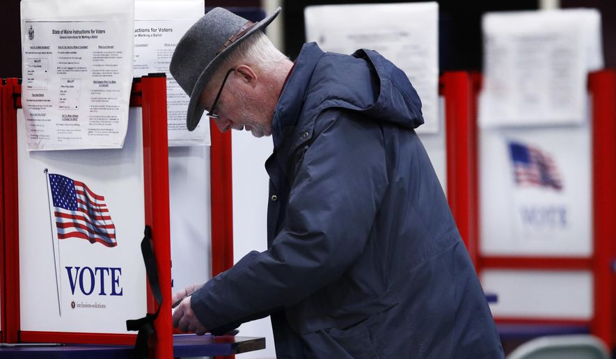 Mike Walsh votes in the primary election, Tuesday, March 3, 2020, in Freeport, Maine. (AP Photo/Robert F. Bukaty)