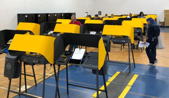 """A sign reads """"Sorry, Out of Order,"""" on a voting station as people cast the ballots Tuesday, March 3, 2020, at the Silverlake Independent Jewish Community Center in Los Angeles. (AP Photo/Justin Pritchard)"""