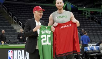 John McEnroe, Captain of Team World for the Laver Cup, trades jerseys with Boston Celtics forward Gordon Hayward before a game against the Brooklyn Nets, Tuesday, March 3, 2020, in Boston. Laver Cup 2020 will be played at the TD Garden in Boston from September 25-27. (AP Photo/Mary Schwalm)