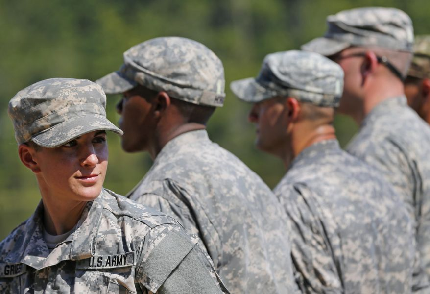 In this Aug. 21, 2015 file photo, U.S. Army Capt. Kristen Griest, left, of Orange, Conn., stands in formation during an Army Ranger School graduation ceremony at Fort Benning, Ga. In arguments to be heard on a college campus, federal appeals court judges on Tuesday, March 3, 2020, will consider whether the military's all-male draft system is constitutional. A Texas-based federal judge ruled last year that it is not, ruling in a lawsuit brought by the National Coalition for Men. The government appealed, leading to Tuesday's hearing before a three judge panel of the 5th U.S. Circuit Court of Appeals. (AP Photo/John Bazemore, File)  **FILE*