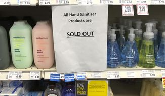 A sign on a shelf at a QFC grocery store in Kirkland, Wash., advises shoppers Tuesday, March 3, 2020 that all hand sanitizer products are sold out. Fear of the coronavirus has led people to stock up on the germ-killing gel, leaving store shelves empty and online retailers with sky-high prices set by those trying to profit on the rush. The store is located near the Life Care Center of Kirkland, which has been tied to several cases of the COVID-19 coronavirus. (AP Photo/Ted S. Warren)