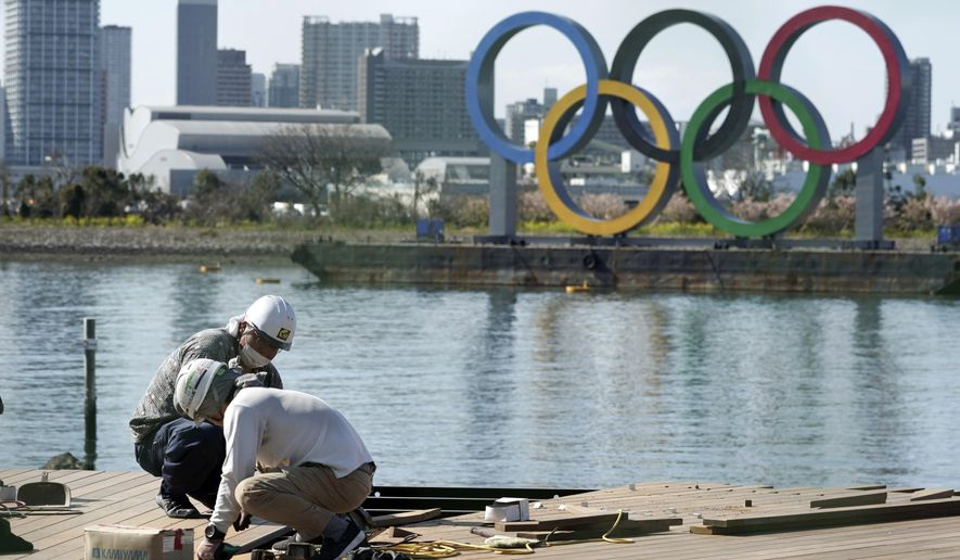 Men work at a construction site with the Olympic rings in the background Tuesday, March 3, 2020, at Tokyo's Odaiba district. The spreading virus from China has put the Tokyo Olympics at risk. The Olympics are to open on July 24 - less than five months away. (AP Photo/Eugene Hoshiko)