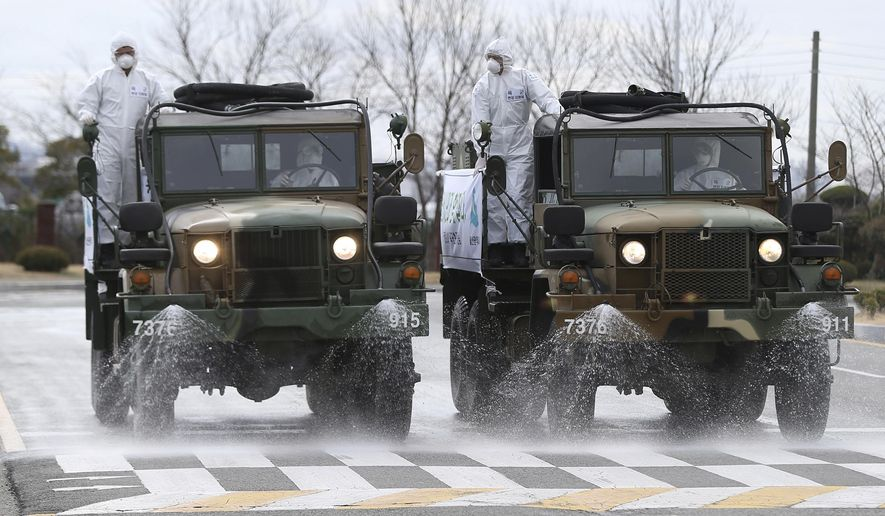 South Korean army trucks spray disinfectant as a precaution against the coronavirus on a street in Ulsan, South Korea, Tuesday, March 3, 2020. China's coronavirus caseload continued to wane Tuesday even as the epidemic took a firmer hold beyond Asia. (Kim Young-tae/Yonhap via AP)