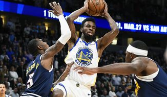 Golden State Warriors Andrew Wiggins (22) looks to make a pass as Denver Nuggets Will Baton lll (5) defends during the first half of an NBA basketball game Tuesday, March 3, 2020 in Denver (AP Photo/John Leyba)