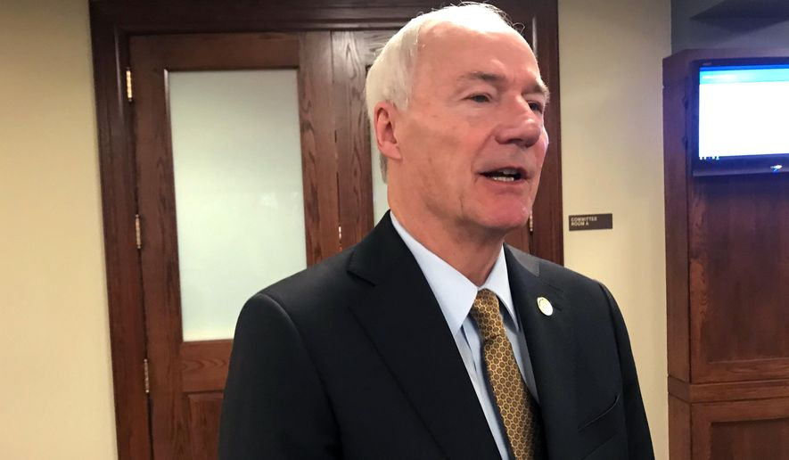 Arkansas Gov. Asa Hutchinson talks to reporters in Little Rock, Arkansas on Wednesday, March 4, 2020 after presenting his proposed budget for the coming fiscal year. (AP Photo/Andrew DeMillo)