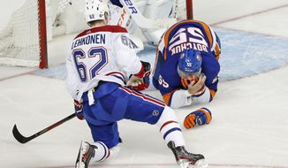 Montreal Canadiens left wing Artturi Lehkonen (62) watches as New York Islanders defenseman Johnny Boychuk (55) clutches his face after Lehkonen's skate hit him on the face during the third period of an NHL hockey game, Tuesday, March 3, 2020, in New York. The Canadiens won 6-2. (AP Photo/Kathy Willens)