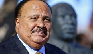 FILE - In this Jan. 25, 2018, file photo, Martin Luther King III stands next to a bust of his father, the Rev. Martin Luther King Jr., during a wreath laying ceremony on, at Kansas State University in Manhattan, Kan. King, as well as family members of Nathaniel Woods, a condemned Alabama inmate, are asking the governor to to stop his execution. Woods is scheduled to be executed on Thursday, March 5, 2020. Woods and co-defendant Kerry Spencer were convicted of capital murder for the 2004 killings of three Birmingham police officers. Spencer was also sentenced to death for the killings. (Chris Neal/The Topeka Capital-Journal via AP, File)
