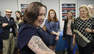 Democratic U.S. Senate candidate MJ Hegar shows her tattoo to supporters during her election night party in Austin, Texas, Tuesday, March 3, 2020. (AP Photo/Eric Gay)