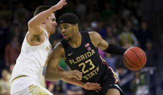 Florida State's M.J. Walker (23) drives as Notre Dame's Nate Laszewski defends during the first half of an NCAA college basketball game Wednesday, March 4, 2020, in South Bend, Ind. (AP Photo/Robert Franklin)