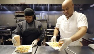 In this Jan. 29, 2020, photo, chef Samara Henderson, left, works with trainee Anthony Redmond at Inspiration Kitchens in Chicago. Redmond, 44, started receiving food stamps when he was released from prison last summer. With the help, he was able to leave a halfway house and find his own place. After the training, he hopes to find employment and keep his benefits. (AP Photo/Nam Y. Huh)