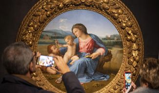Visitors take photos of Raphael's painting Virgin with Child and Infant St. John the Baptist, at a press preview of Raphael's exhibition in Rome, Wednesday, March 4, 2020. The paintings,  drawings and sketches in the most ambitious assemblage ever of Raphael works in an exhibition, more than even the Renaissance superstar had in his workshop at one time, are collectively insured for 4 billion euros, against the likes of theft or vandalism. But no money can guarantee that Italy's outbreak of coronavirus, the largest in Europe, won't play havoc with the three-month run in Rome of the art world's eagerly-awaited blockbuster. (AP Photo/Domenico Stinellis)