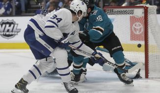 Toronto Maple Leafs center Auston Matthews, left, scores a goal against the San Jose Sharks during the second period of an NHL hockey game in San Jose, Calif., Tuesday, March 3, 2020. (AP Photo/Jeff Chiu)