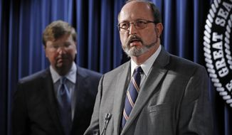 Mississippi Republican Gov. Tate Reeves, left, listens as Bob Anderson, the new state Department of Human Services director, speaks about his appointment, Wednesday, March 4, 2020, in Jackson, Miss. Anderson is an attorney who has led the Medicaid fraud division of the state attorney general's office. (AP Photo/Rogelio V. Solis)