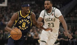 Indiana Pacers' Justin Holiday drives past Milwaukee Bucks' Sterling Brown during the first half of an NBA basketball game Wednesday, March 4, 2020, in Milwaukee. (AP Photo/Morry Gash)