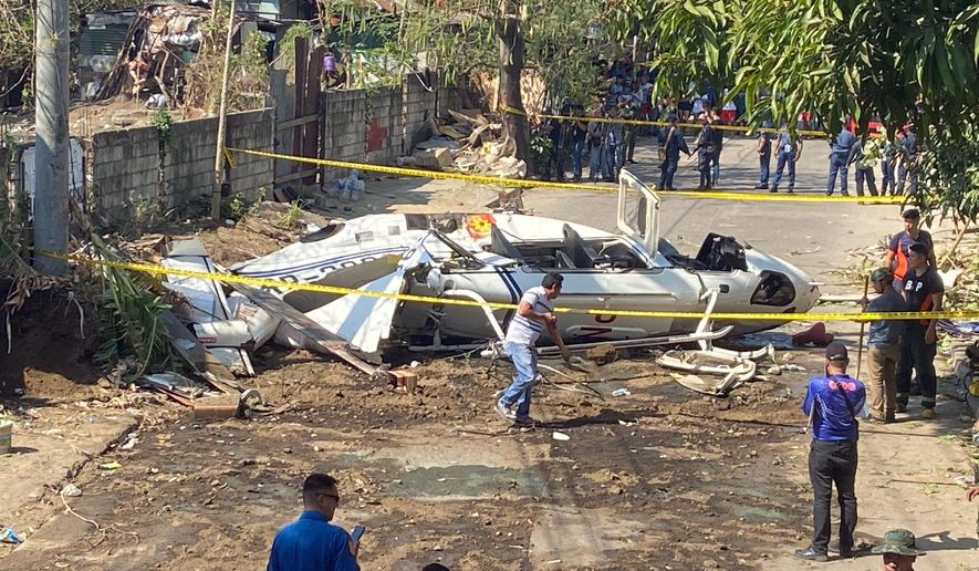 The site of a helicopter crash is cordoned off in San Pedro, Laguna province, south of Manila, Philippines Thursday, march 5, 2020.  The helicopter carrying the Philippine national police chief and other people crashed Thursday, officials said. (AP Photo/Aaron Favila)