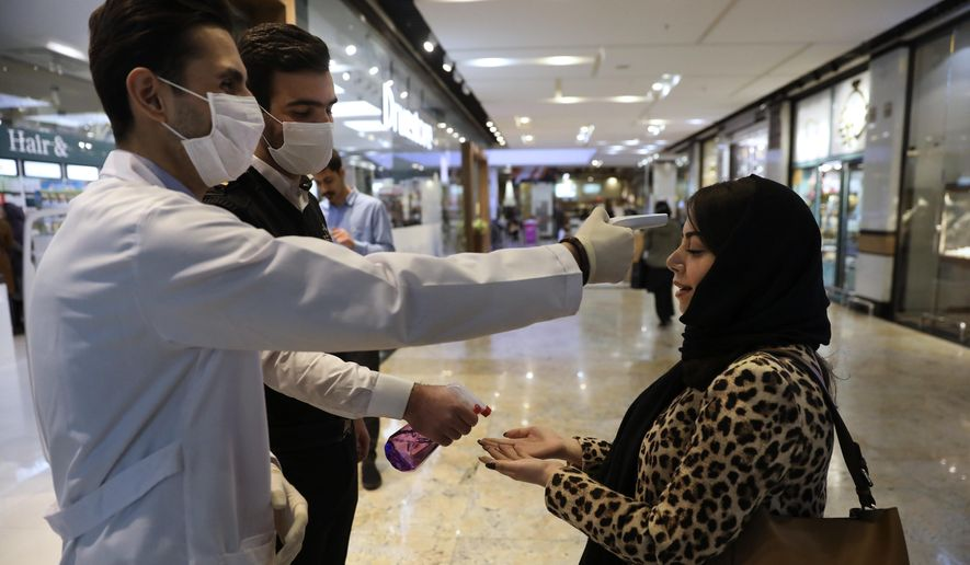 A woman has her temperature checked and her hands disinfected as she enters the Palladium Shopping Center, in northern Tehran, Iran, Tuesday, March 3, 2020. Iran's supreme leader put the Islamic Republic's armed forces on alert Tuesday to assist health officials in combating the outbreak of the new coronavirus, the deadliest outside of China. (AP Photo/Vahid Salemi)