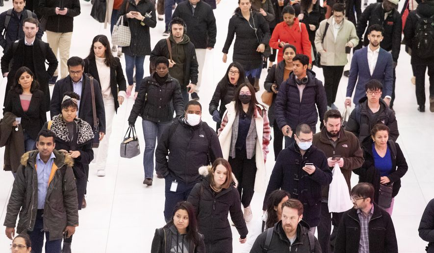 Three commuters, center, wear masks as they walk through the World Trade Center transportation hub, Wednesday, March 4, 2020, in New York. (AP Photo/Mark Lennihan)
