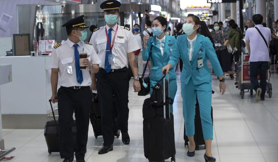 Flight crew wear protective masks as they arrive at the Suvarnabhumi Airport in Bangkok, Thailand, Wednesday, March 4, 2020. (AP Photo/Sakchai Lalit)