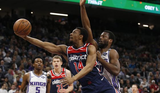 Washington Wizards guard Ish Smith, left, goes to the basket past Sacramento Kings forward Harrison Barnes, right, during the first quarter of an NBA basketball game in Sacramento, Calif., Tuesday, March 3, 2020. (AP Photo/Rich Pedroncelli) ** FILE **