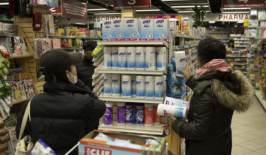 Now a familiar scene: Customers consider sanitizing wipes on the shelves of a pharmacy in New York City. How worried are we? (Associated Press)