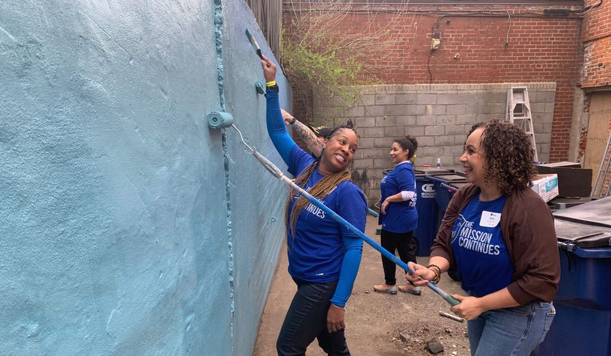 Veterans Jamicka Edwards (left) and Elis Salamone from The Mission Continues' women's leadership fellowship program repaint the outdoor space at Calvary Women's Services on Thursday in the District. (Sophie Kaplan/The Washington Times)