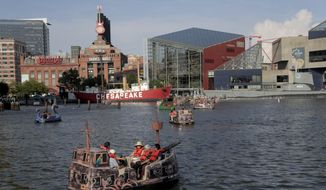 People relax on an electric boat in Baltimore's Inner Harbor, Friday, July 5, 2019. After a day of mostly sunshine, the Baltimore area is expected to see showers throughout the weekend. (AP Photo/Julio Cortez)  **FILE**