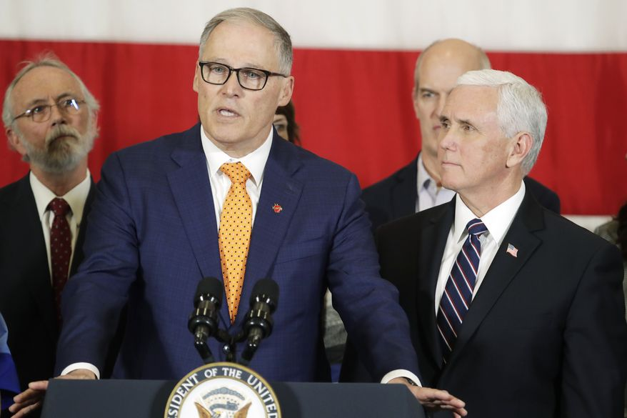 Vice President Mike Pence, right, looks on as Gov. Jay Inslee speaks during a news conference, Thursday, March 5, 2020, at Camp Murray in Washington state. Pence was in Washington to discuss the state's efforts to fight the spread of the COVID-19 coronavirus. (AP Photo/Ted S. Warren)
