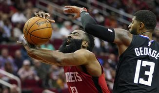 Houston Rockets' James Harden, left, is fouled by Los Angeles Clippers' Paul George during the second half of an NBA basketball game Thursday, March 5, 2020, in Houston. The Clippers won 120-105. (AP Photo/David J. Phillip)