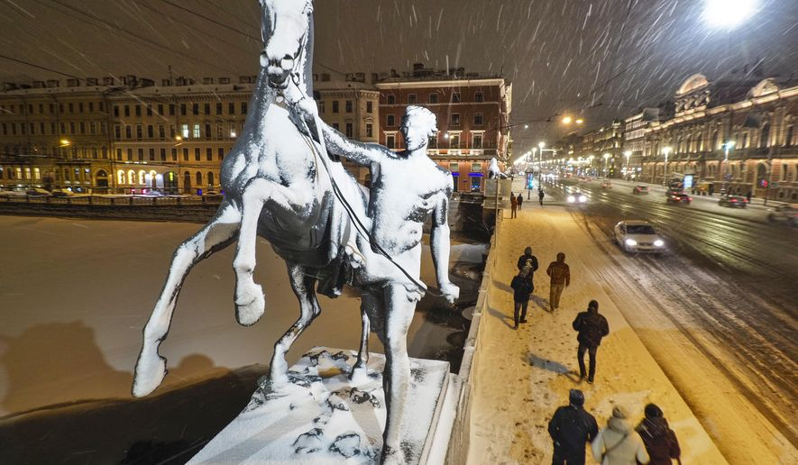 People walk in snowfall past one of the four famous horse sculptures of the Anichkov Bridge on the Fontanka River in St.Petersburg, Russia, Thursday, Feb. 6, 2020. A cyclone has caused snowfall in St. Petersburg. (AP Photo/Dmitri Lovetsky)