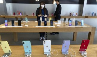 In this Feb. 26, 2020, photo, a worker polishes iPhones in an Apple store in Beijing. (AP Photo/Ng Han Guan)