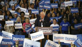 Supporters of Democratic presidential candidate Sen. Bernie Sanders, I-Vt., waves signs as Sanders speaks at a campaign rally Thursday, March 5, 2020, in Phoenix. (AP Photo/Ross D. Franklin)