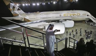 "FILE- In this Thursday, Dec. 18, 2014 file photo, an Emirati man takes a selfie in front of a new Etihad Airways A380 in Abu Dhabi, United Arab Emirates. Abu Dhabi's long-troubled national carrier Etihad on Thursday, March 5, 2020, reported losses of $870 million in 2019 after losing billions in recent years, calling the result ""encouraging."" (AP Photo/Kamran Jebreili, File)"