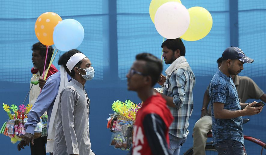 An Indian wears a mask and walks on a street in Hyderabad, India, Thursday, March 5, 2020. A new virus first detected in China has infected more than 90,000 people globally and caused over 3,100 deaths. The World Health Organization has named the illness COVID-19, referring to its origin late last year and the coronavirus that causes it. (AP Photo/Mahesh Kumar A.)