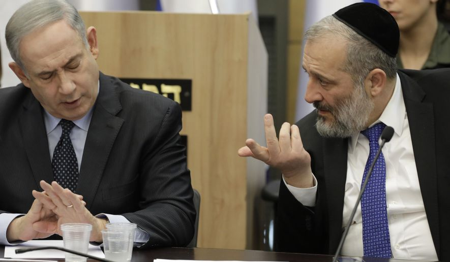 Israeli Prime Minister Benjamin Netanyahu listens to Israeli Interior Minister Aryeh Deri during a meeting with his nationalist allies and his Likud party members, at the Knesset, Israeli Parliament, in Jerusalem, Wednesday, March 4, 2020. (AP Photo/Sebastian Scheiner)
