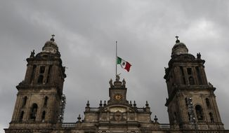 In this Sept. 9, 2017, file photo, a Mexican flag flies at half-mast on the Metropolitan Cathedral during three days of mourning following a deadly earthquake and hurricane, in Mexico City. (AP Photo/Marco Ugarte, File)