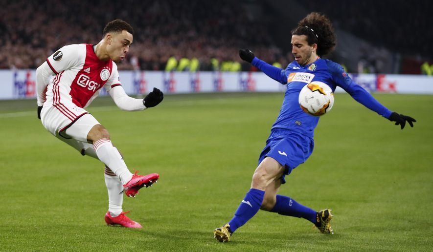Ajax's Sergino Dest, left, and Getafe's Marc Cucurella vie for the ball during a round of 32, second leg, Europa League soccer match between Ajax and Getafe at the Johan Cruyff ArenA in Amsterdam, Netherlands, Thursday, Feb. 27, 2020. (AP Photo/Peter Dejong)